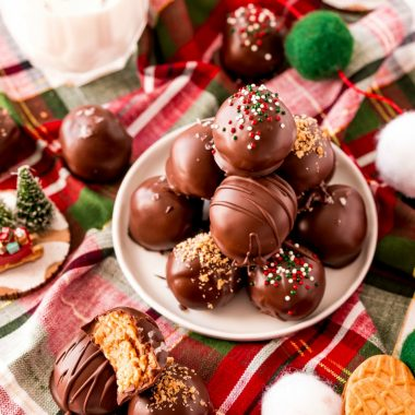 Nutter Butter Truffles made with 5 basic ingredients & perfect for holiday goodie trays! Festive, easy cookie balls with Nutter butters, cream cheese, peanut butter & chocolate!