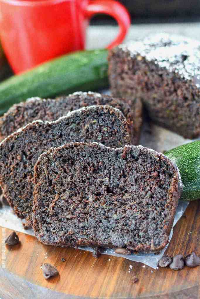 chocolate zucchini bread on a cutting board with zucchini