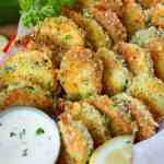 zucchini parmesan crisps in a basket with a side of ranch dressing