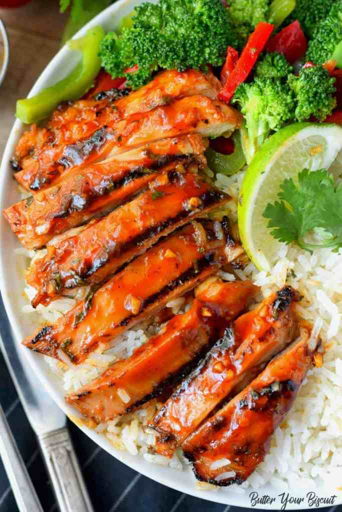 Honey sriracha grilled chicken over coconut rice with a lime slice