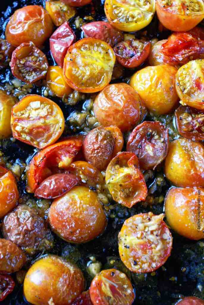 Garlic roasted cherry tomatoes on a baking sheet