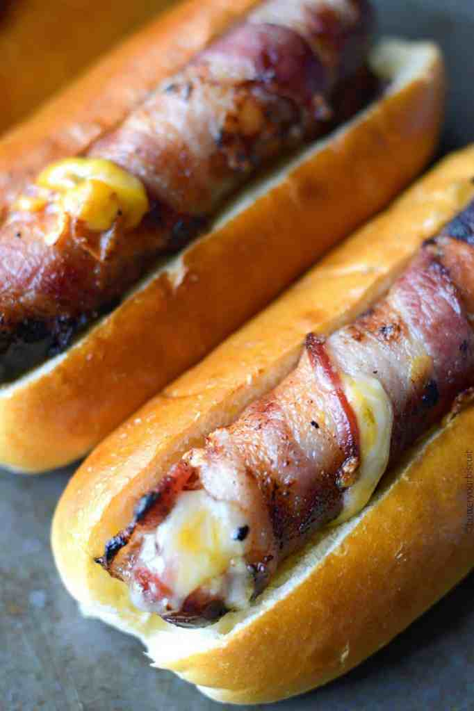 Bacon wrapped hot dogs stuffed with cheese in soft buns