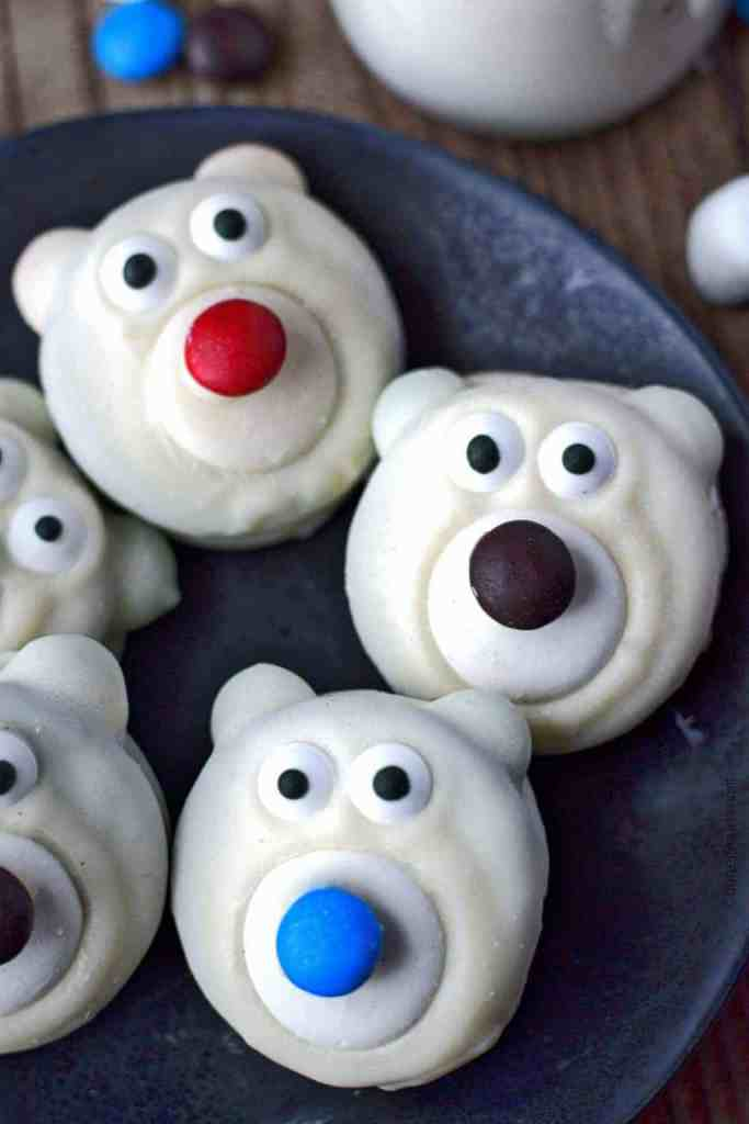 Polar bear cookies on a black plate with milk