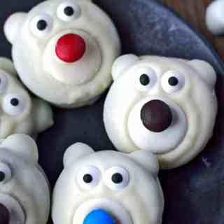 Polar bear cookies on a black plate with milk