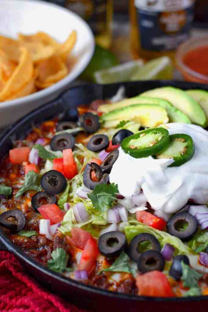 Loaded taco dip in a skillet with chips