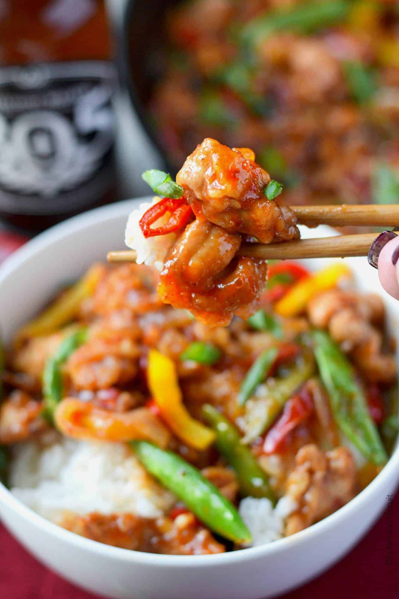 Sweet and Spicy chicken stir fry bite with chopsticks