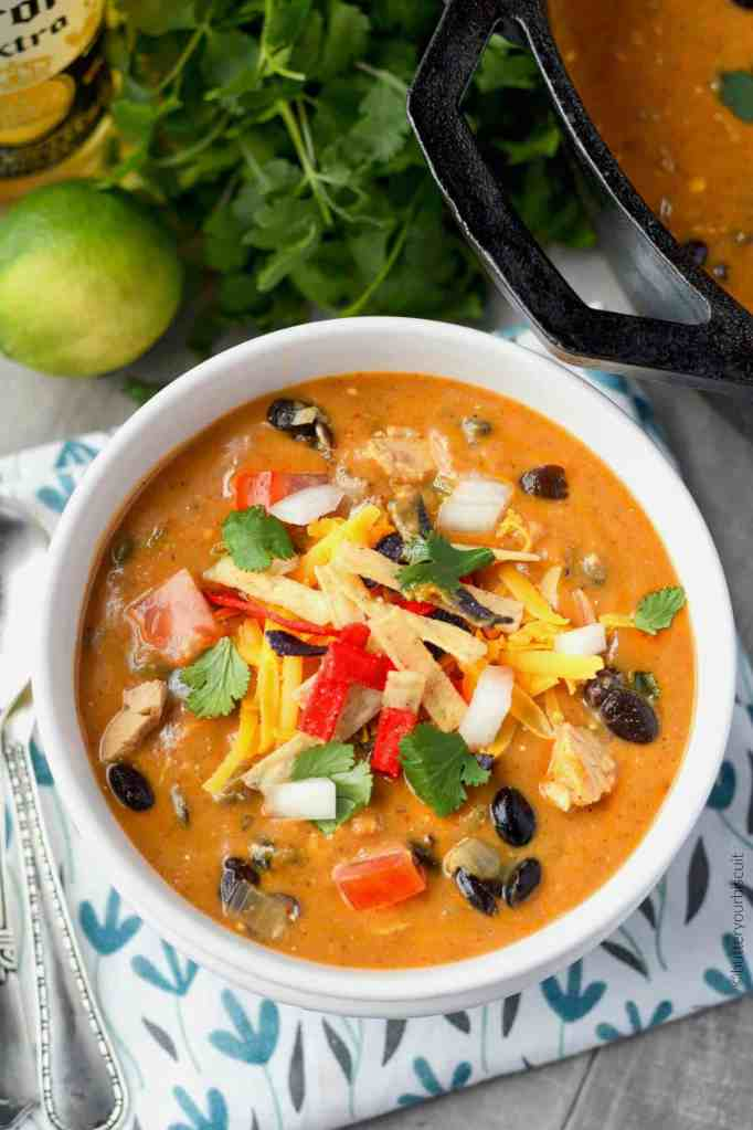 Chilis copycat chicken enchilada soup in a white bowl with toppings
