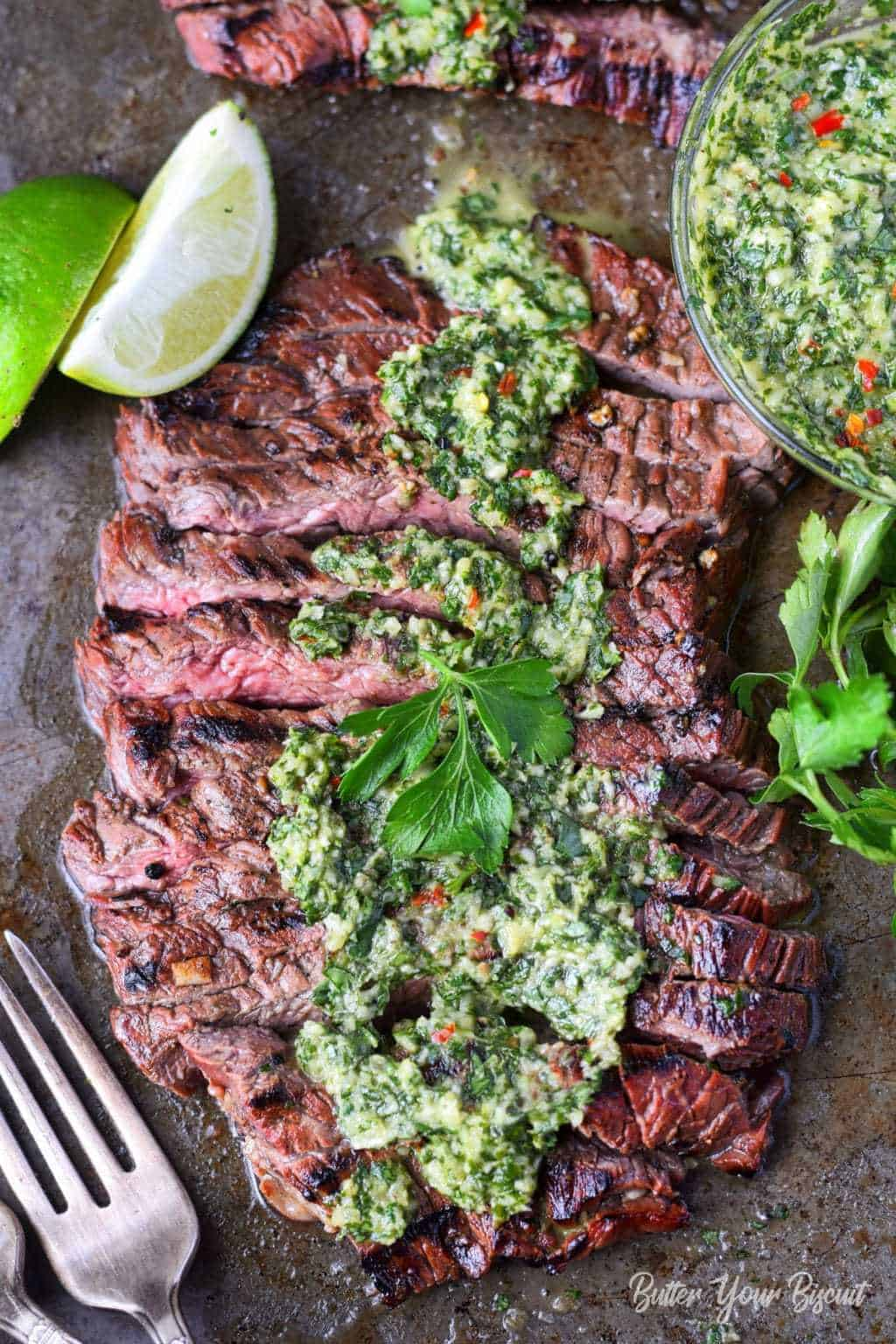 Grilled skirt steak and chimichurri spread on top with forks and lime slices