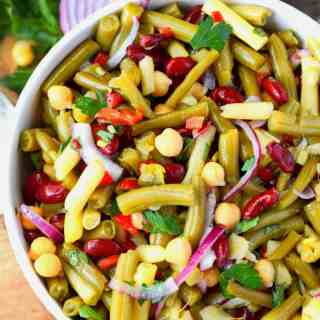 Four bean salad in a large white serving bowl