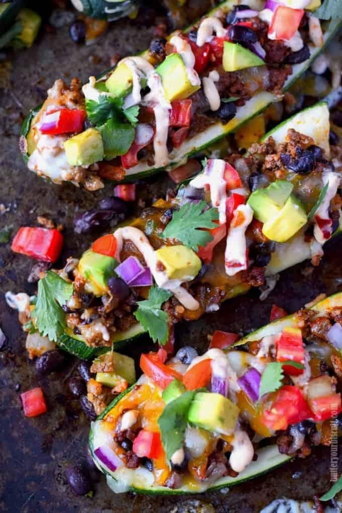 Taco stuffed zucchini boats on a baking sheet