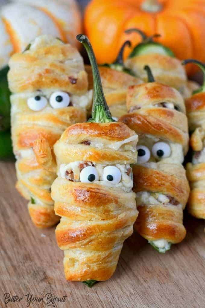 bacon jalapeno mummies piled on a cutting board with some pumpkins in the back