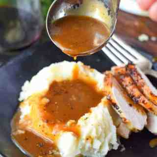 make ahead turkey gravy on top of mashed potatoes and turkey on a black plate
