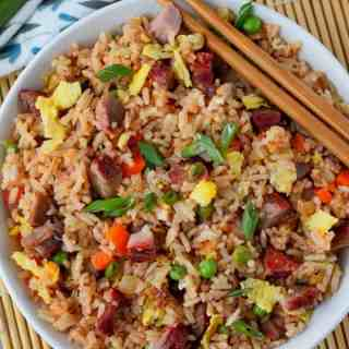 pork fried rice in a white bowl with chopsticks