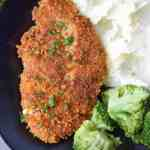 crispy chicken cutlets on a black plate with mashed potatoes and broccoli