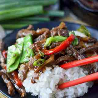 Beef stir fry with white rice on a black plate and red chopsticks