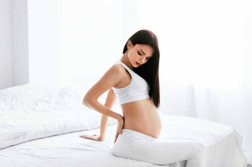 Pregnant woman holding back in pain