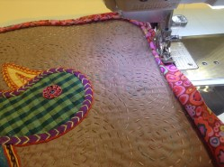 Sewing on the pipping onto the Sri Lankan appliqué pillow cover.