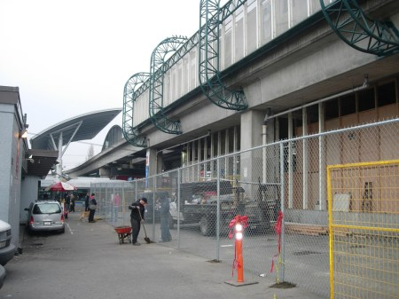 Fencing is now up in the lane by Broadway Station's entrance, in preparation for the installation of the west glass wall.