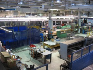 The panel fabrication area on the body shop floor. The blue curtained area houses the plasma cutter.