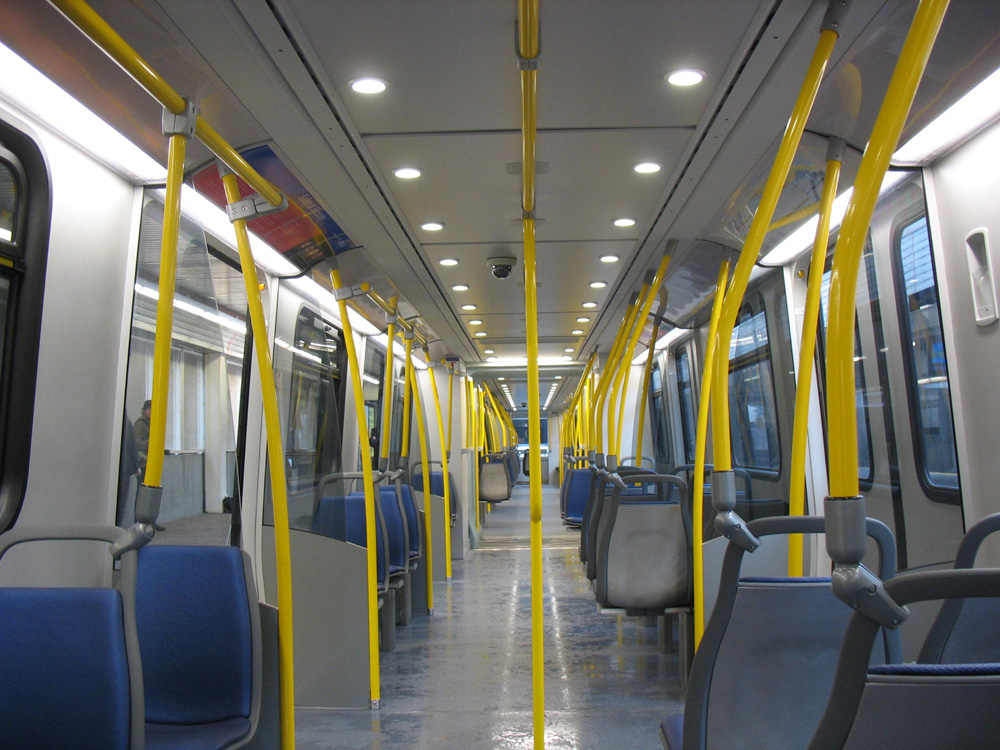 Interior of ART Mark II trains in Vancouver, British Columbia - the yellow coatings are antibacterial.  Take note that, along with the floor-to-ceiling bars (stanchions) there is a grab bar running through the centre of the carriage roof.