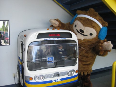 Quatchi plays with a miniature bus at Surrey Transit Centre.