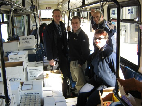 CMBC staff members stand in the bus full of food donations.