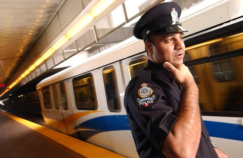 """Transit Police uniforms are black, with  """"POLICE"""" across the back of the jackets in silver. Their trousers have a medium blue stripe on the outside seam and their shoulder patches read """"Safely Linking Communities."""""""
