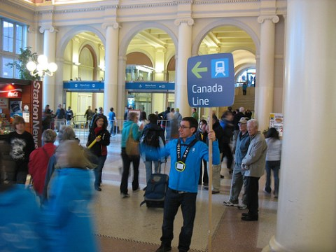 A transit host holds a Canada Line sign.