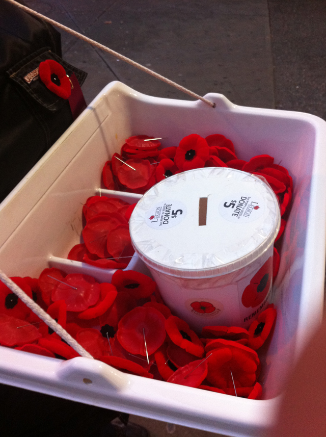 A tray of poppies being sold outside of a SkyTrain station.