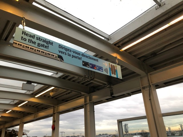 New bilingual signs at the YVR–Airport Station letting customers they can head straight for the faregates if they have a contactless Visa, Mastercard or American Express credit card.