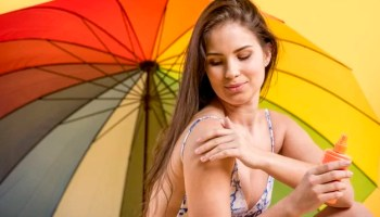 how to remove tan from hand and legs woman-putting-sunscreen