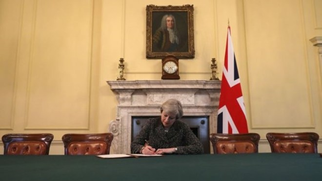 Theresa May signs the letter to the EU confirming the UK's departure