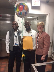 Pierre Adelson, of Food Services, receives a free month of parking as part of the survey raffle. Pictured with supervisor Corliss Hazel (at left) and HR's Ellen Gilmore.