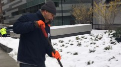Ruberkis Arias, of Environmental Services, shovels snow outside the Hale Building for Transformative Medicine.