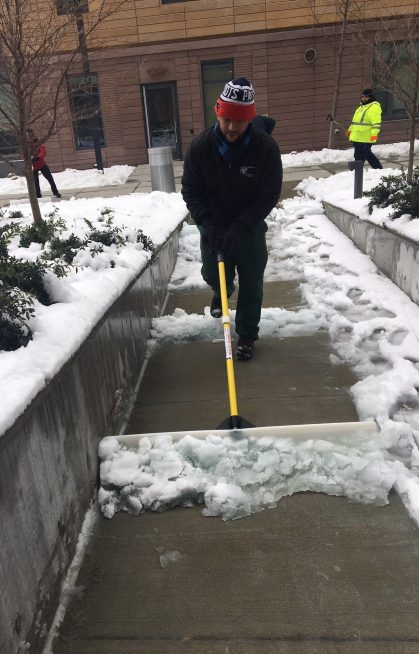 Deibis Soto, of Environmental Services, shovels snow outside the Hale Building for Transformative Medicine.