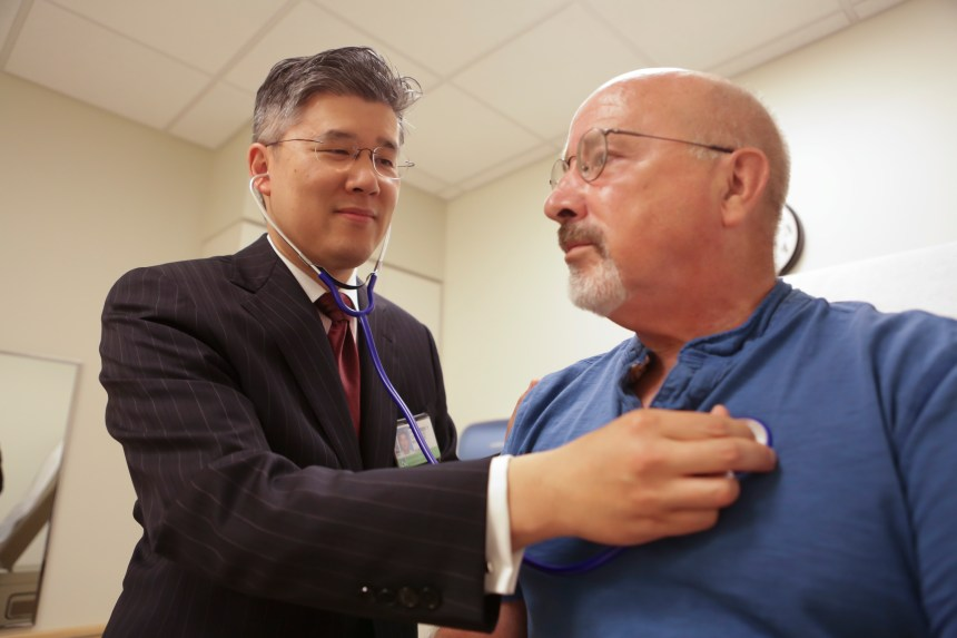 Cardiac Surgeon Fred Chen, MD, PhD, listens to the heart of BWH patient Jim Slate, who is also staff nurse in the Cardiac Surgery ICU at BWH. Cardiology and Heart Surgery were among BWH specialties that ranked among the top 10 in this year's U.S. News & World Report.