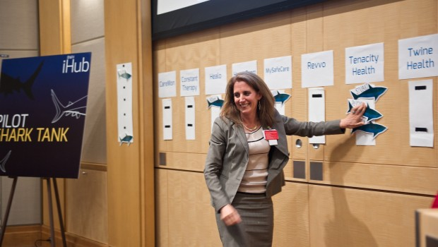"""Jessica Dudley, chief medical officer, Brigham and Women's Physician's Organization, shows her interest in partnering with Tenacity Health by placing her name—among those of other interested """"sharks"""" —on the wall."""