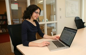 Rebecca Weintraub, MD, faculty director of the Global Health Delivery Project and associate physician in the BWH Division of Global Health Equity, reads a posting in one of GHDonline's communities.