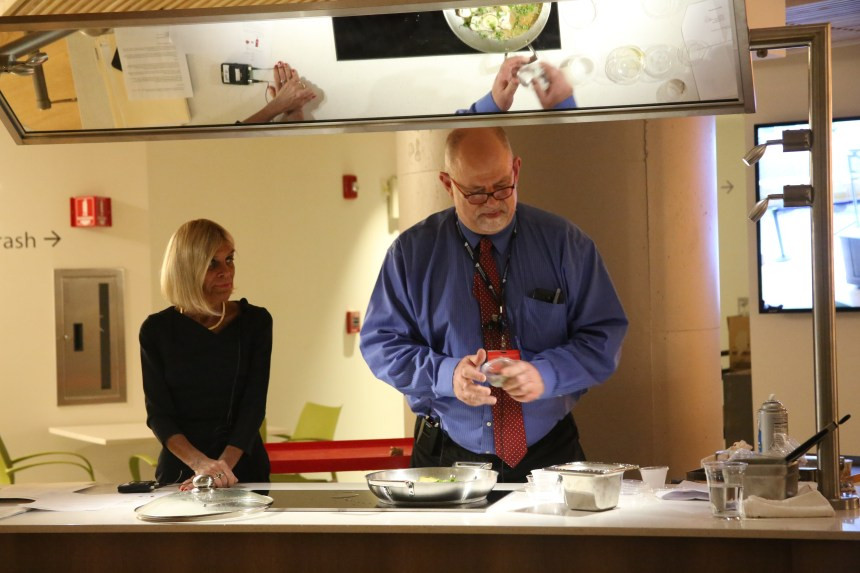 "Kathy McManus watches Chef Peter Lamb make a Cilantro Lime Haddock dish during a ""Let's Get Cooking"" session."