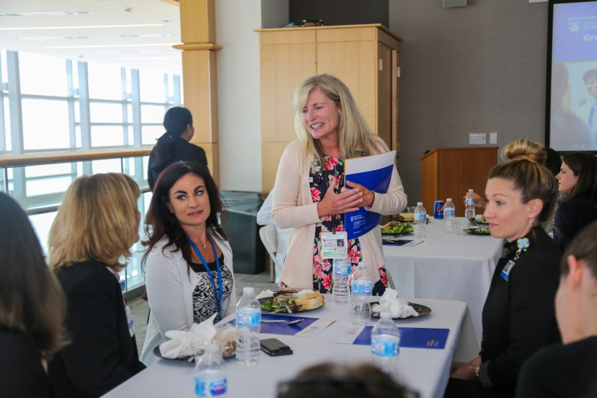 Elisa Frederick, standing, speaks with Elaine Joyal, left and foundation scholarship recipients Tanya Martel, second from left, and Kasey Moffat, right, during the reception.
