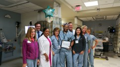 Nurse leaders and colleagues surprise Marino Long-Mella (center, holding certificate) with exciting news.