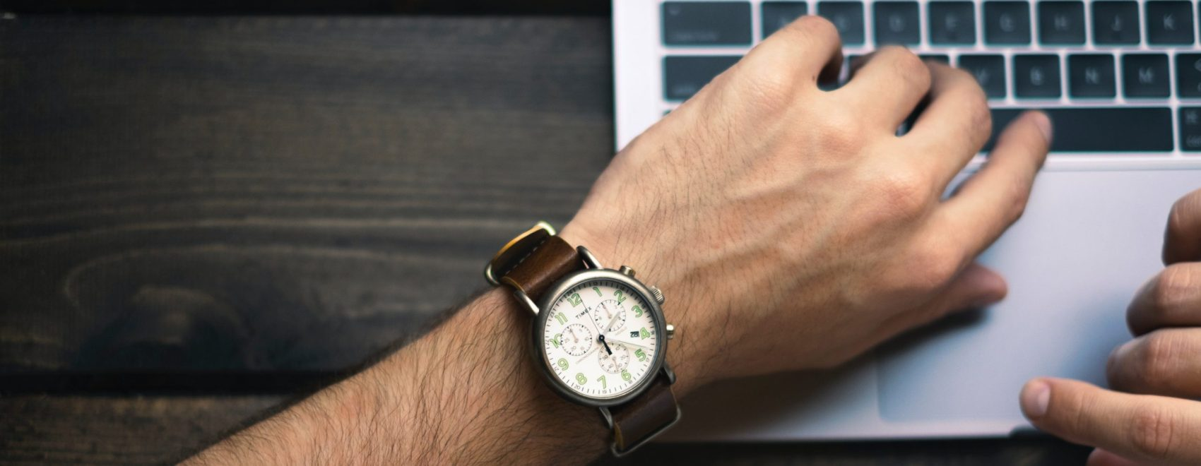 Image of watch on arm and laptop