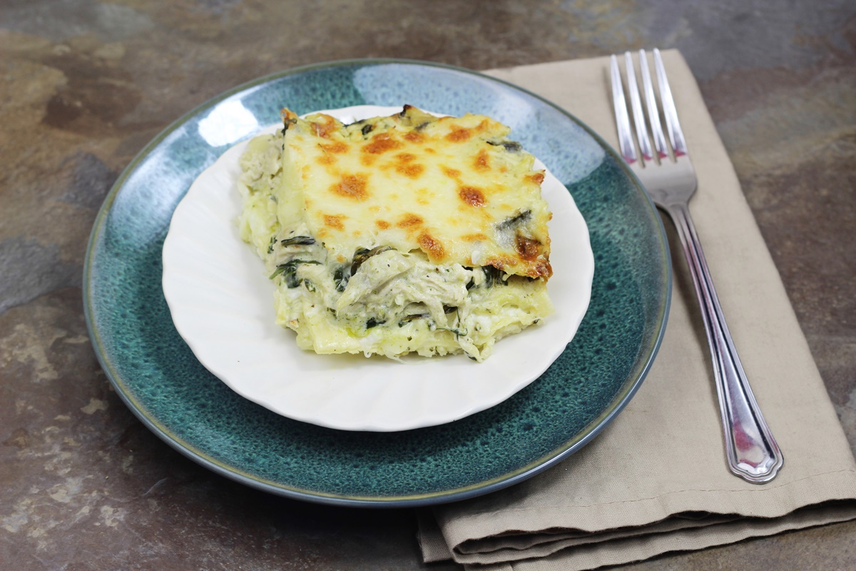 Plated Instant Pot Chicken Spinach Artichoke Lasagna on a white plate, sitting on a green plate, with a tan napkin and fork.