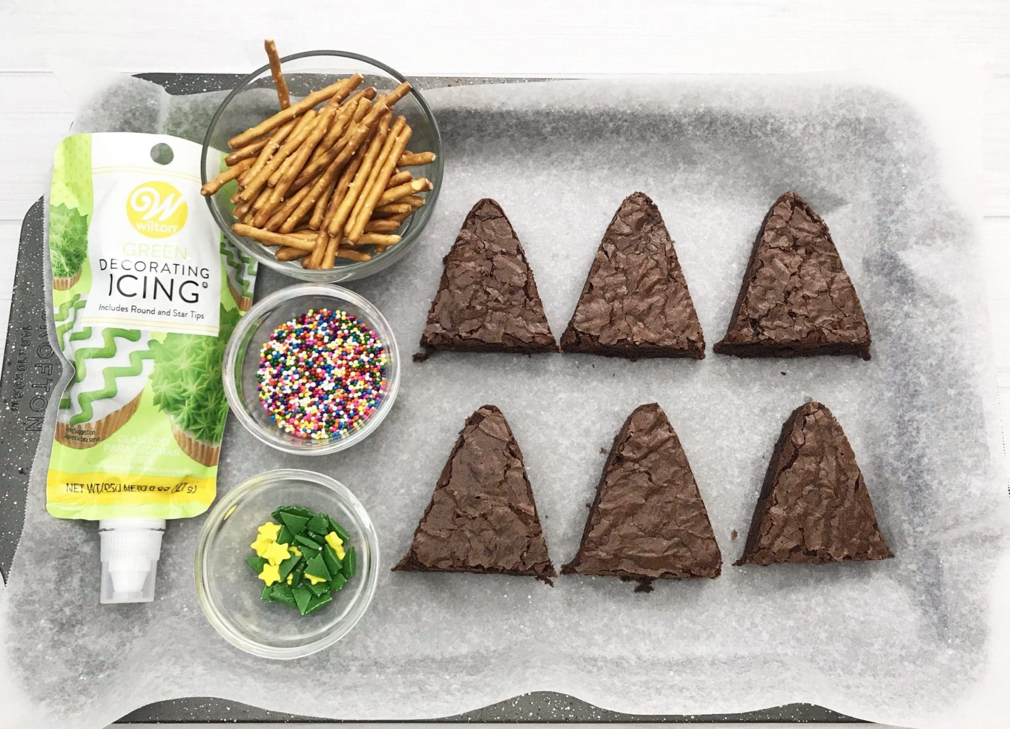 triangle brownie next to sprinkles, pretzel sticks, frosting and stars