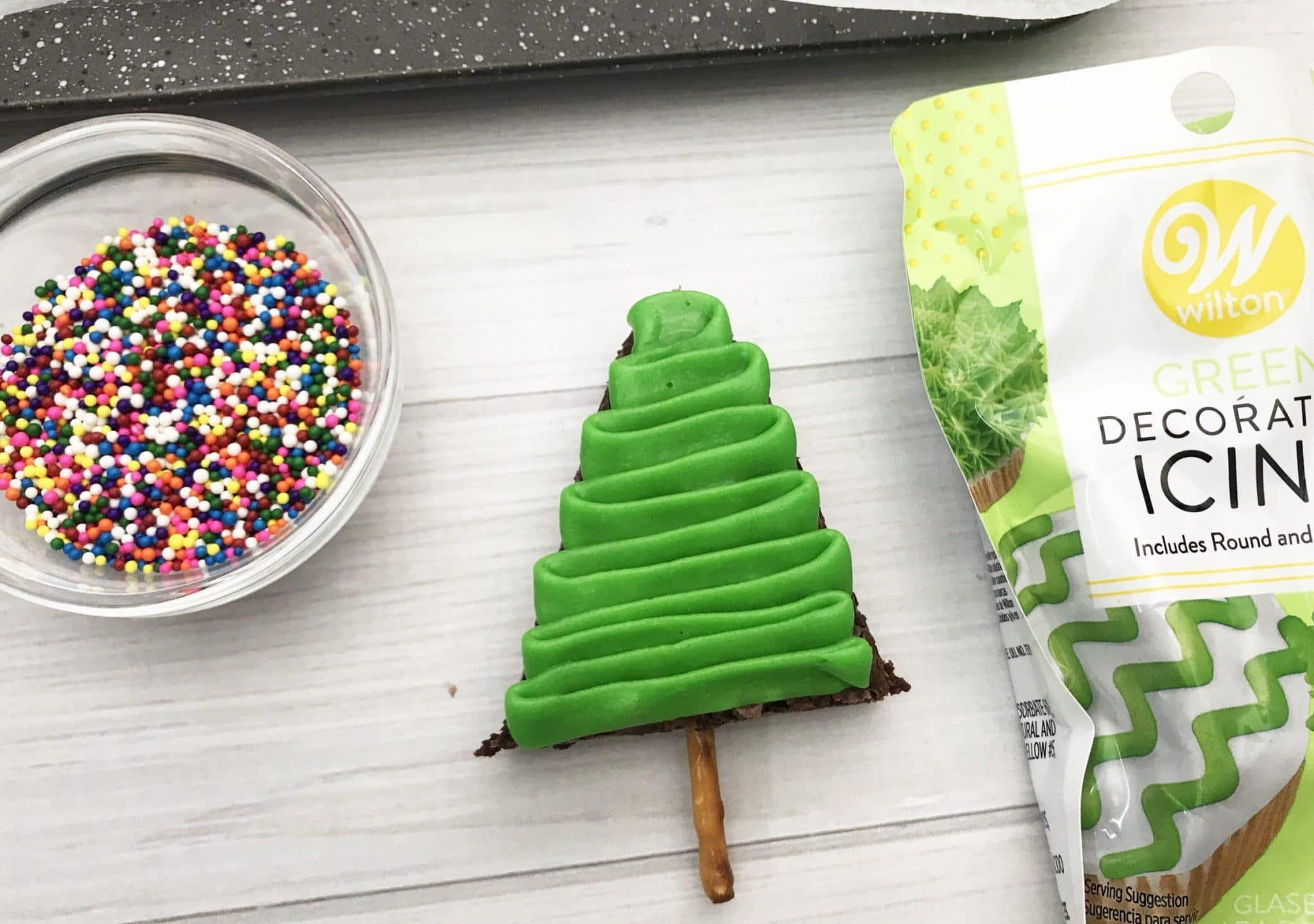 christmas tree brownie, iced with green icing next to colorful sprinkles