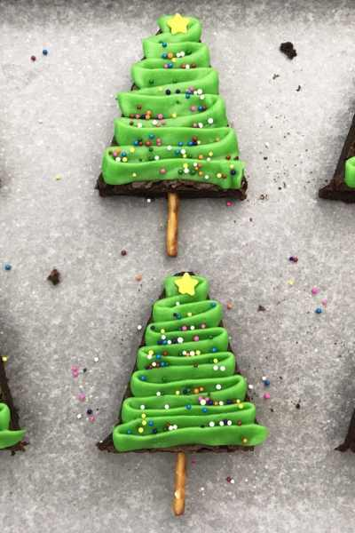 christmas tree brownies on a baking sheet with parchment paper, decorated with green icing, sprinkles and a star