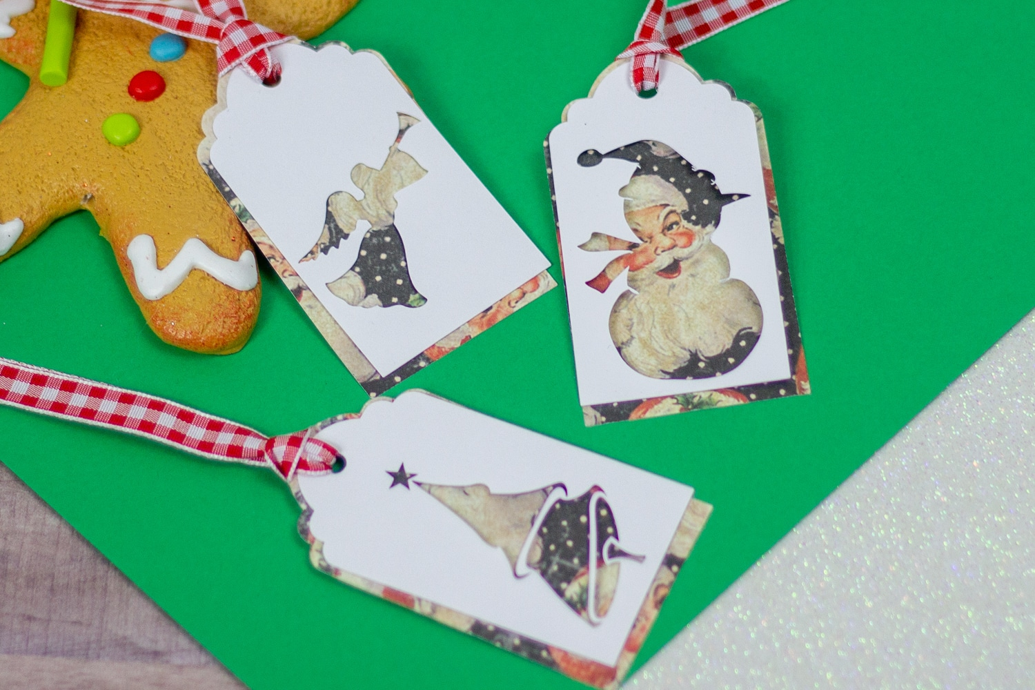 Image of Christmas Gift Tags that have Christmas graphics on them with green background and part of a gingerbread man showing.