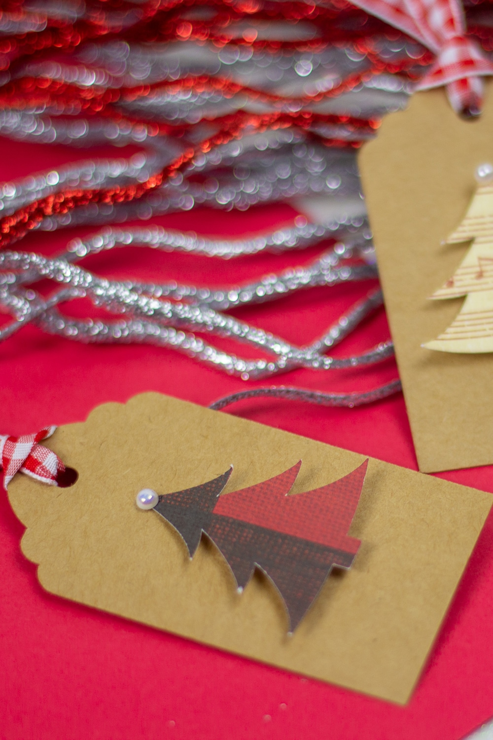 Image of a Christmas tree gift tag with red and silver gilttery pip cleaners in the background.