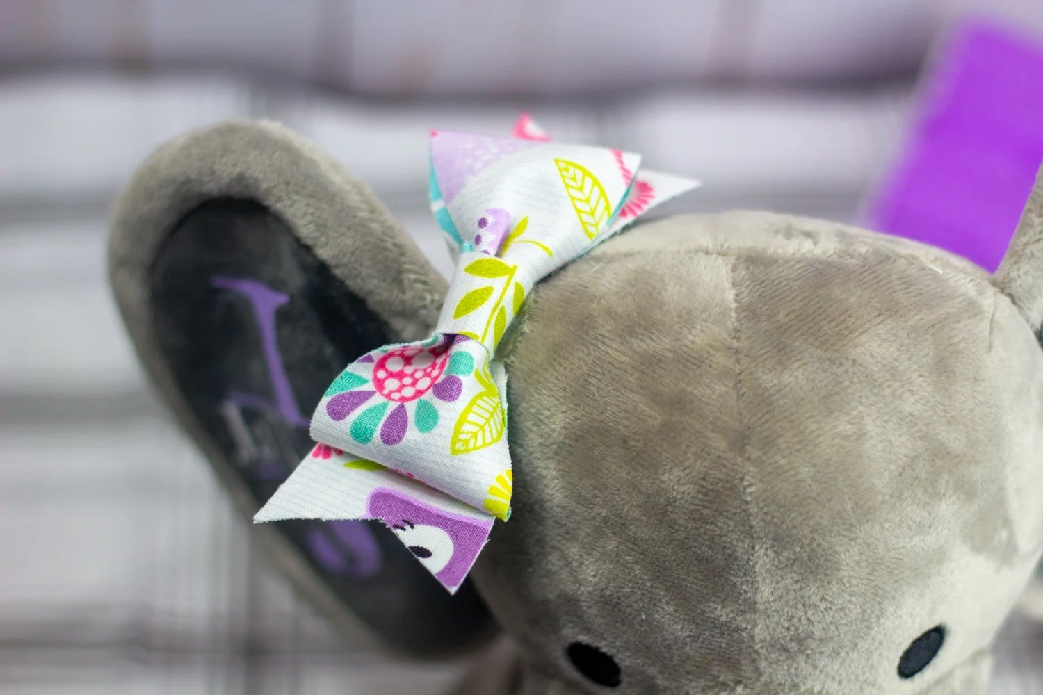close up of cricut maker no sew fabric bow attached to a birth stat elephant that is gray