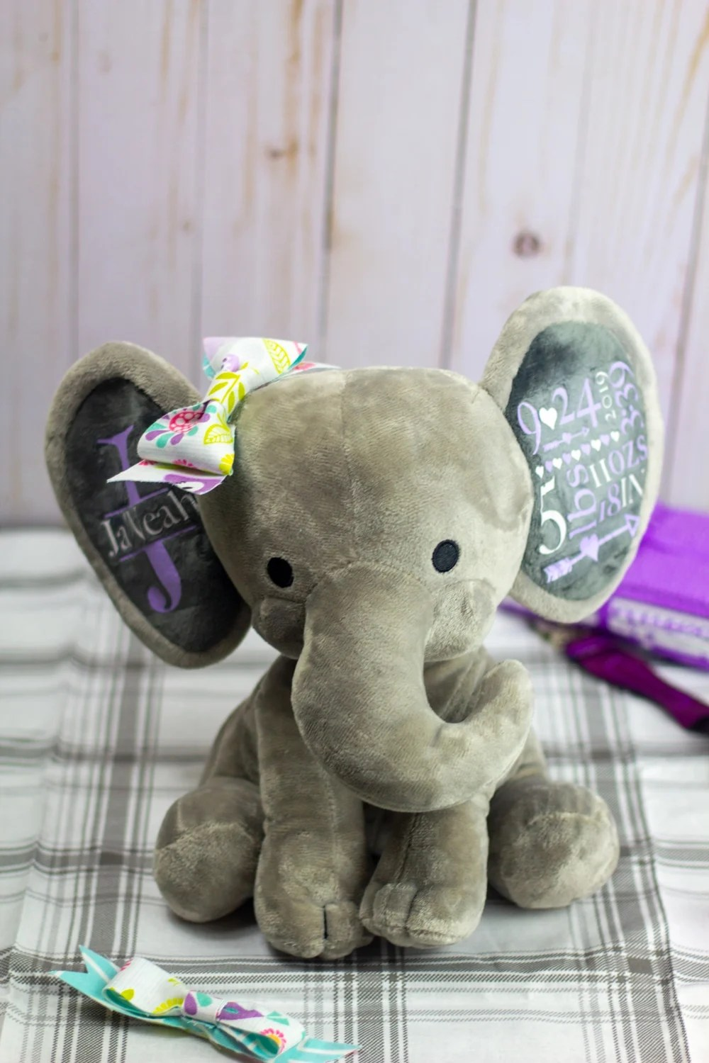 personalized stuffed animal gray elephant with fabric bow and purple and white text on the ears
